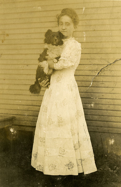 [Woman holding a dog]